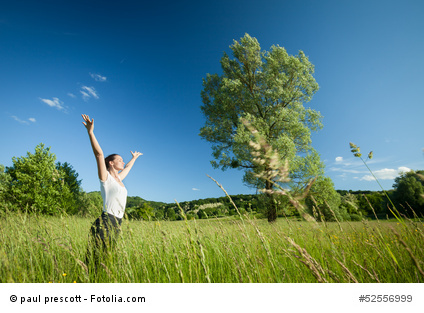 Young beautifull woman relaxing with arms raised in nature with tree in background and grass in foreground.