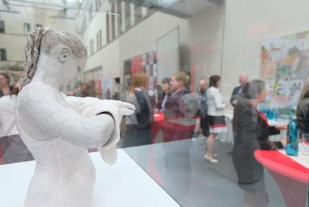 """Veranstaltungs-Impression aus der Kundenhalle der NASPA Hauptverwaltung in Wiesbaden. Im Vordergrund Skulptur """"Puppenspieler"""" von Stephanie Marie Roos der Ausstellung © Foto: Diether v. Goddenthow"""
